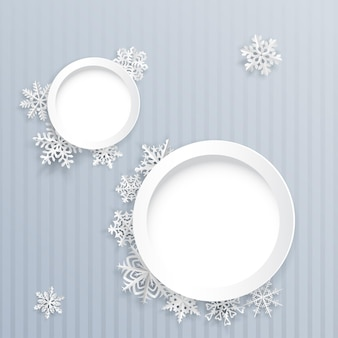 Kerstachtergrond met twee ronde frames en papieren sneeuwvlokken op grijs gestreepte achtergrond