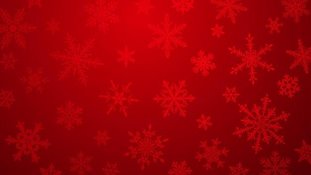 Kerstachtergrond met verschillende complexe grote en kleine sneeuwvlokken in rode kleuren