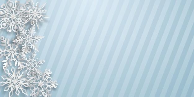 Kerstachtergrond met verschillende papieren sneeuwvlokken met zachte schaduwen op een lichtblauwe gestreepte achtergrond