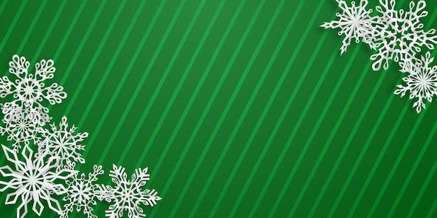 Kerstachtergrond met verschillende papieren sneeuwvlokken met zachte schaduwen op groen gestreepte achtergrond