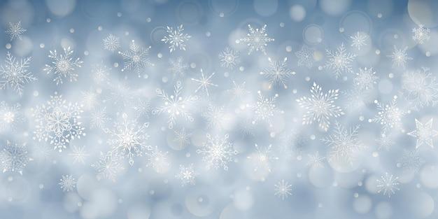 Kerstachtergrond van complexe grote en kleine vallende sneeuwvlokken in lichtblauwe kleuren met bokeh-effect