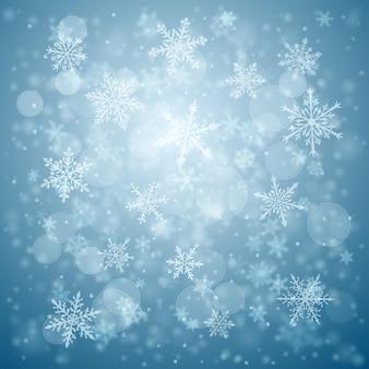 Kerstachtergrond van complexe wazige en heldere vallende sneeuwvlokken in blauwe kleuren met bokeh-effect