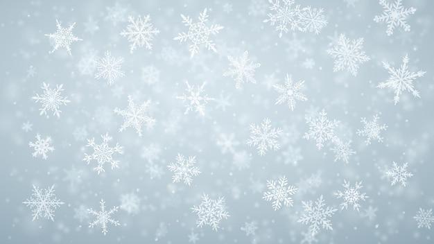 Kerstachtergrond van complexe wazige en heldere vallende sneeuwvlokken in lichtblauwe kleuren met bokeh-effect