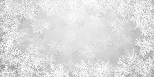 Kerstachtergrond van grote complexe sneeuwvlokken in grijze kleuren