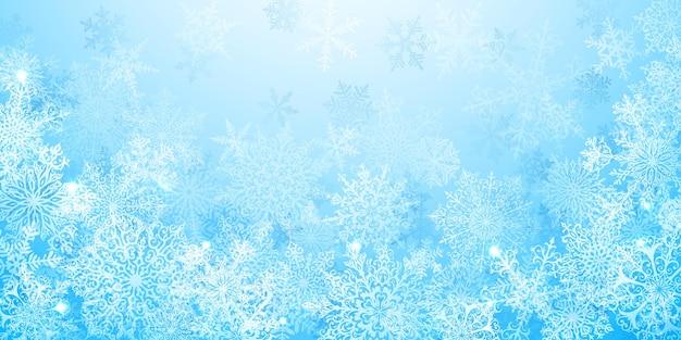 Kerstachtergrond van grote complexe sneeuwvlokken in lichtblauwe kleuren