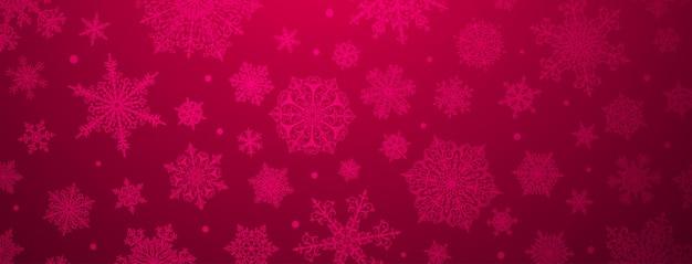 Kerstachtergrond van grote en kleine complexe sneeuwvlokken in karmozijnrode kleuren