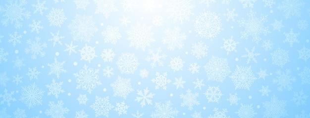 Kerstachtergrond van grote en kleine complexe sneeuwvlokken in lichtblauwe kleuren