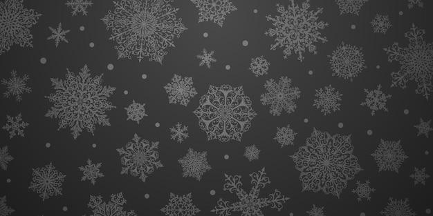 Kerstachtergrond van grote en kleine complexe sneeuwvlokken in zwarte kleuren