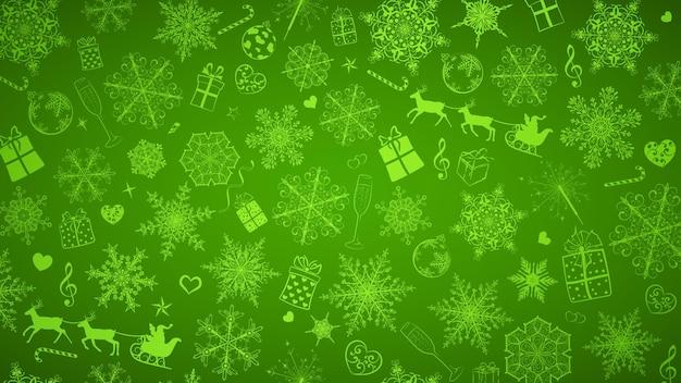 Kerstachtergrond van grote en kleine sneeuwvlokken en verschillende kerstsymbolen, wit op groen