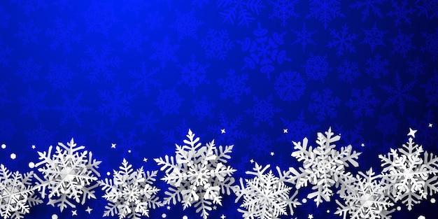 Kerstachtergrond van papieren sneeuwvlokken met zachte schaduwen, wit op blauwe achtergrond met vallende sneeuw