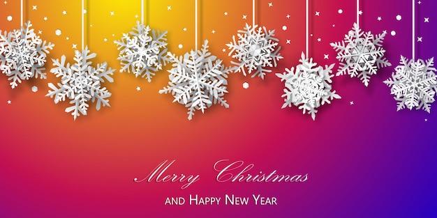 Kerstachtergrond van papieren sneeuwvlokken met zachte schaduwen, wit op paarse en oranje achtergrond