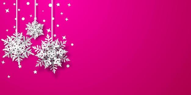 Kerstachtergrond van papieren sneeuwvlokken met zachte schaduwen, wit op roze achtergrond