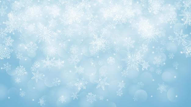 Kerstachtergrond van vallende sneeuwvlokken in lichtblauwe kleuren met bokeh-effect