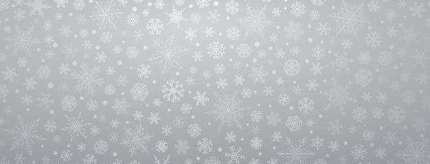Kerstachtergrond van verschillende complexe grote en kleine sneeuwvlokken, in grijze kleuren