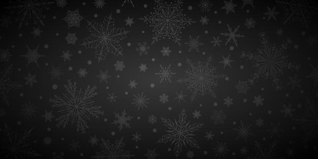 Kerstachtergrond van verschillende complexe grote en kleine sneeuwvlokken, in zwarte kleuren
