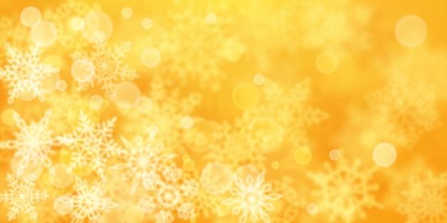Kerstachtergrond van wazige sneeuwvlokken in gele kleuren