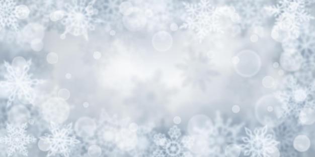 Kerstachtergrond van wazige sneeuwvlokken in grijze kleuren
