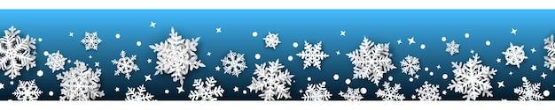 Kerstbanner van papieren sneeuwvlokken met zachte schaduwen, wit op een lichtblauwe achtergrond. met naadloze horizontale herhaling