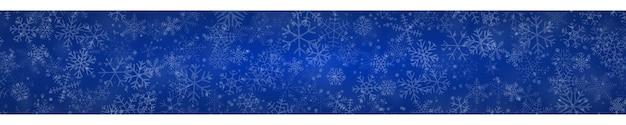 Kerstbanner van sneeuwvlokken in verschillende vormen, maten en transparantie op blauwe achtergrond