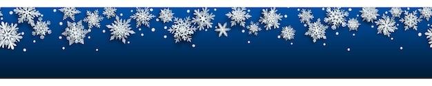Kerstbanner van witte complexe papieren sneeuwvlokken met zachte schaduwen op blauwe achtergrond. met horizontale herhaling