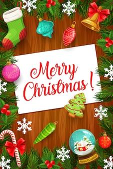 Kerstboom en holly berry takken met kerstcadeaus en wenskaart. wintervakantie frame met zuurstokken, sneeuwvlokken en bel, sok, ornament ballen en peperkoek op houten achtergrond