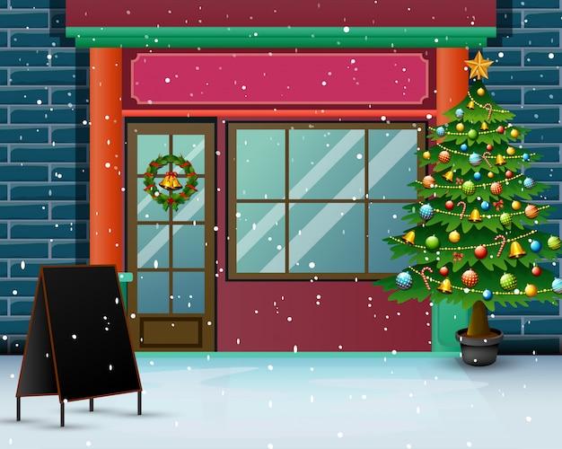 Kerstboom vooraan de winkel met sneeuwval