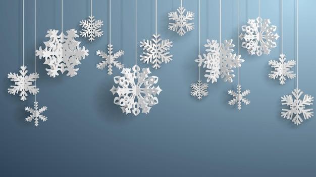 Kerstillustratie met witte driedimensionale papieren sneeuwvlokken die op een grijze achtergrond hangen