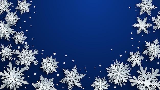 Kerstillustratie van witte complexe papieren sneeuwvlokken met zachte schaduwen op blauwe achtergrond