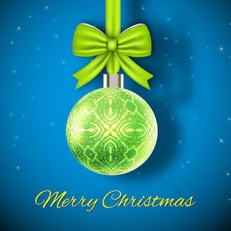 Kerstkaart gloeiende groene kerstbal op blauw