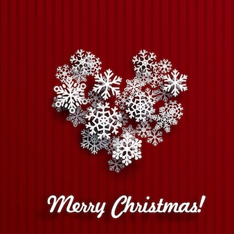 Kerstkaart met hart gemaakt van witte sneeuwvlokken op rood gestreepte achtergrond