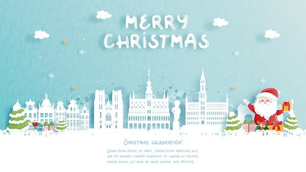Kerstkaart met reizen naar belgië concept. leuke kerstman en geschenkdozen. wereldberoemde bezienswaardigheid in papier gesneden stijl illustratie.