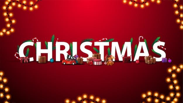 Kerstkaart met witte grote volumetrische 3d-tekst versierd met kerstboomtakken, snoep en kerstcadeaus