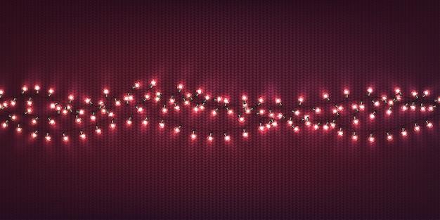 Kerstlichten. kerstmis gloeiende slingers van led-lampen op paarse gebreide textuur.