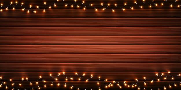 Kerstlichten. kerstmis gloeiende slingers van leidene gloeilampen op houten achtergrond