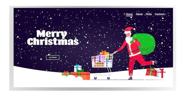 Kerstman duwen trolley kar met cadeau huidige dozen kerst verkoop vakantie viering shopping concept sneeuwval achtergrond bestemmingspagina