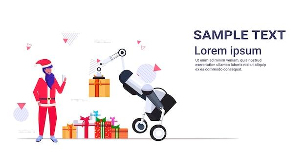 Kerstman met behulp van mobiele app die industriële robot bestuurt die geschenkdozen draagt vrolijk kerstfeest, gelukkig nieuwjaar, wintervakantie