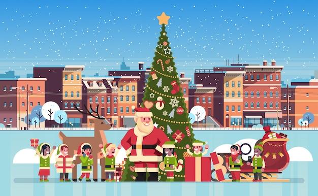 Kerstman mix race elf rendieren in de buurt van versierde dennenboom stad bouwen huizen