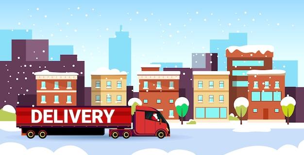 Kerstman rijden levering semi vrachtwagen met geschenkdoos container verzending vervoer voor vrolijk kerstfeest gelukkig nieuwjaar besneeuwde stad straat moderne stadsgezicht achtergrond horizontaal