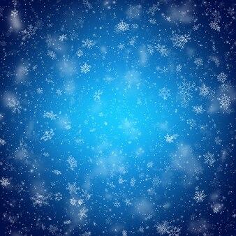 Kerstmis met witte wazig en duidelijk sneeuwvlokken op blauwe achtergrond.