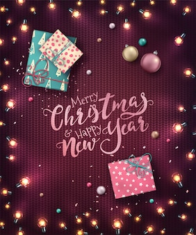 Kerstmisachtergrond met kerstmislichten, snuisterijen, giftdozen en confettien. vakantie gloeiende slingers van led-lampen op gebreide textuur