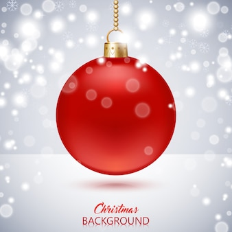Kerstmisachtergrond met rode kerstmisbal en sneeuwval.