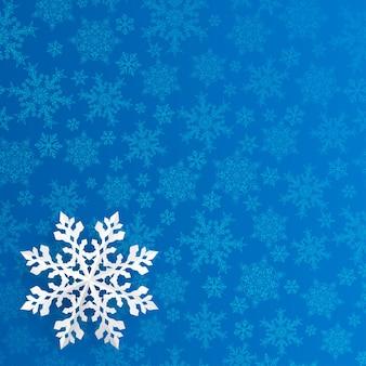 Kerstmisachtergrond met sneeuwvlok gesneden uit papier op blauwe achtergrond van kleine sneeuwvlokken