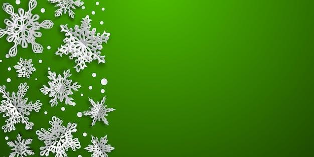 Kerstmisachtergrond met volumedocument sneeuwvlokken met zachte schaduwen op groene achtergrond