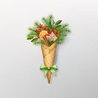 Kerstmissamenstelling in een wafelkegel van naaldtakken, giftdoos en decoraties