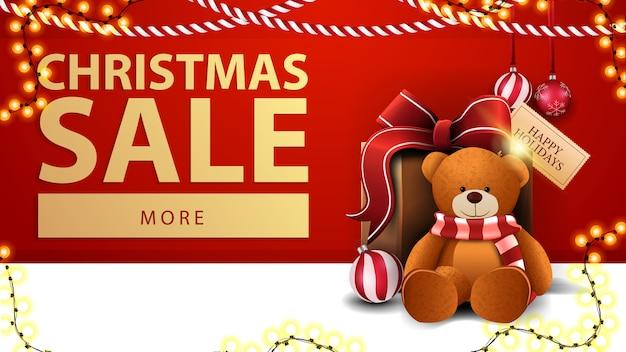 Kerstmisverkoop, rode kortingsbanner met slingers, knoop en teddybeer dichtbij de muur