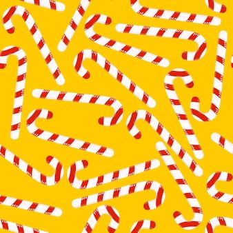Kerstpatroon met kleurrijk gestreept snoep in de vorm van een stok op een gele achtergrond.
