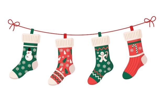 Kerstsokken met verschillende traditionele kleurrijke vakantieornamenten. hangende kinderkledingelementen met schattige kerstpatronen aan touw. rode, groene sokken met sneeuwvlokken, sneeuwpop, kerstboom
