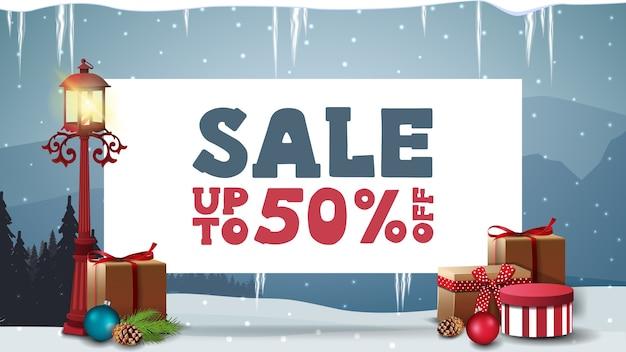 Kerstuitverkoop, tot 50 korting, kortingsbanner met wit vel papier met aanbieding, paallantaarn, cadeautjes en blauw winterlandschap