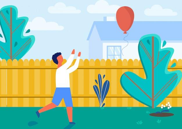 Kind dat op de binnenplaats van het huis met ballon speelt.