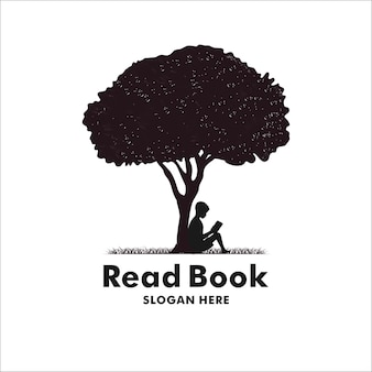 Kind leest een boek onder een boom